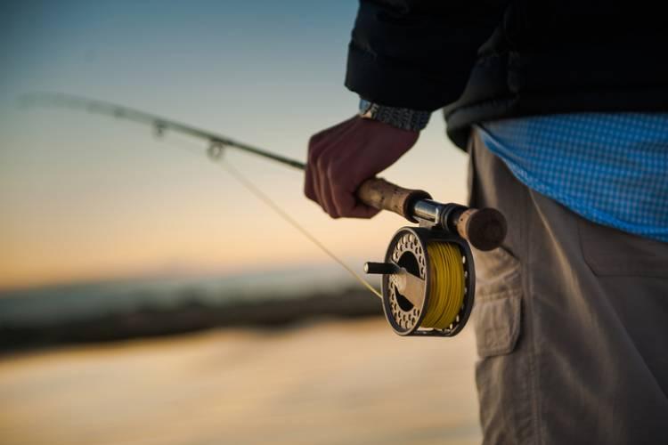 A man holds a fishing pole