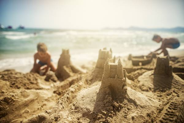Children build a sandcastle at a Port A beach